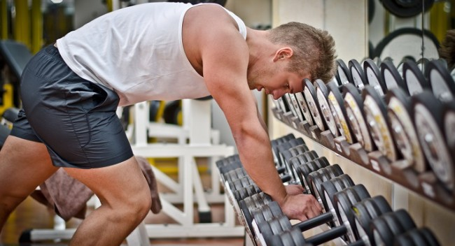 Handsome young athletic man resting on dumbells rack after workout in gym